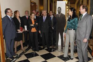 El presidente del Senado, Pío García-Escudero, y la presidenta del Parlamento gallego, Pilar Rojo (derecha de la foto), junto a una imagen de la exposición en la que aparece Mariano Rajoy.