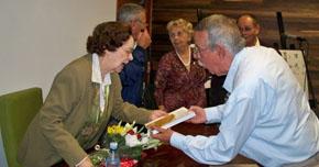 El delegado de España Exterior en Cuba, Manuel Barros, entrega el libro a la conferenciante.