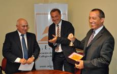 El nuevo presidente de AEGU, Héctor Álvarez, el embajador Roberto Varela y el presidente saliente, Jorge Expósito, muestra el regalo que recibió.