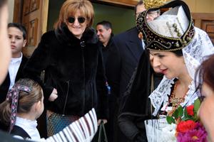 La consejera saluda a una niña, ambas ataviadas con el traje típico.