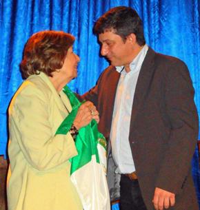 La presidenta del Centro Andaluz recibió emocionada la bandera de Andalucía de manos del director de la Agencia Andaluza de Cooperación Internacional para el Desarrollo.