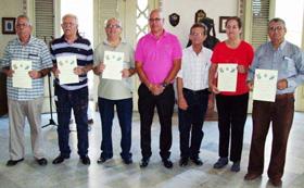 Juan Caridad Fernández, presidenta de 'Hijos del Ayuntamiento de Capela', firmando ejemplares del libro 'Puentes cordiales entre España y Cuba'.