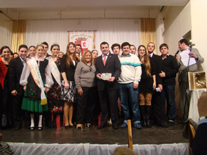 La presidenta del Centro de La Plata, Alicia Vega, entregó la placa a Adrián Iglesias, presidente de la Subcomisión de Jóvenes (ambos en el centro de la imagen).