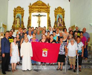 Los asistentes a la celebración y el padre Cuevas posan con la bandera de León.