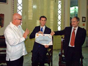 El presidente de la FSGC, Sergio Toledo (izquierda), entregó a Feijóo el Título de Presidente de Honor, ante el embajador español, Juan Francisco Montalbán.