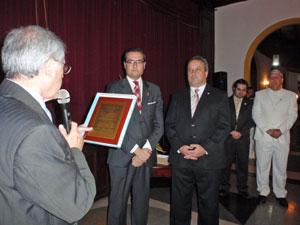 Antonio Alamo lee la placa que la directiva del Hermandad Canaria entregó como reconocimiento a  Moisés Morera Martín, segundo por la izquierda.