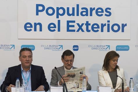 Rajoy consulta un ejemplar de España Exterior al inicio de la reunión con Alfredo Prada y María Dolores de Cospedal.