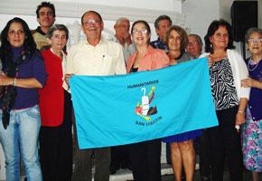 El presidente Longinos Valdés Álvarez y la directiva Aleida Gutiérrez, rodeados por socios de la entidad.