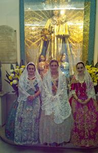 Jóvenes ataviadas con los trajes típicos de Valencia frente al altar de la Virgen de los Desamparados.