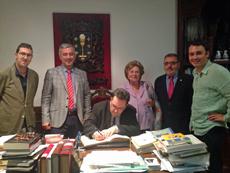 Autoridades que asistieron a la inauguración de la muestra firmando en el libro de honor del Centro Galego.