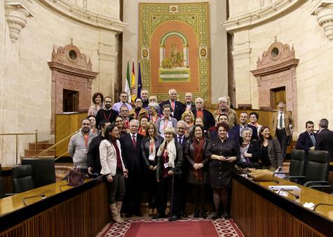 El consejero de la Presidencia, Manuel Jiménez Barrios (centro), el diputado Francisco Menacho (a la izquierda) y represantes de la Junta posan con miembros de las asociaciones de emigrantes retornados en el Parlamento tras la aprobación.