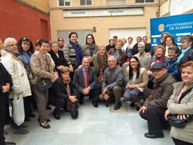 Miembros de Asaler con el alcalde de Almería rodeando la estatua de homenaje al emigrante.