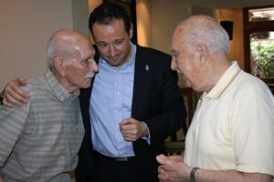 El consejero de Presidencia, Guillermo Martínez, con dos emigrantes asturianos en el Club Tinetense de Buenos Aires.