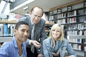 Dos jóvenes estudiantes de español junto a su profesor en la biblioteca del Instituto Cervantes de Berlín.