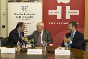 Javier Bello (izq.) saluda a Víctor García de la Concha en presencia de Rafael Rodríguez-Ponga tras la firma del convenio en la sede del Instituto Cervantes en Alcalá de Henares (Madrid).