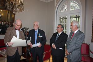 El embajador español Carlos Robles lee el diploma que acompaña a la Medalla de Honor de la Emigración que se le entregó a José Antoni Fanjul, a su izquierda.