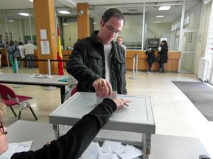 Joven catalán depositando su voto en la urna instalada en el Consulado de España en París.