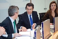 El presidente gallego, Alberto Núñez Feijóo, hablando con el conselleiro de Presidencia, Alfonso Rueda, y al fondo la conselleira de Facenda, Marta Fernández Currás en la reunión del Consello de la Xunta.