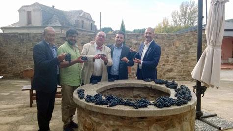 Los responsables de la bodega con varios racimos de uva tras la vendimia.
