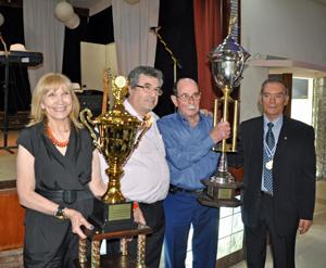 El presidente y la secretaria del Centro Asturiano Casa de Asturias reciben los trofeos.