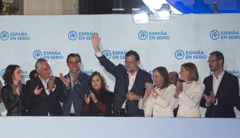 Mariano Rajoy, con su esposa y de dirigentes del PP, saluda a los simpatizantes desde el balcón de la sede de su partido.