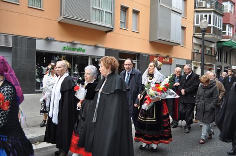 La consejera Milagros Marcos (con un ramo de flores), acompaña a los socios de la entidad en la procesión por las calles de Barcelona.
