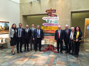 La delegación canaria junto a un cartel con las ciudades hermanadas con San Antonio, entre las que se encuentran Las Palmas y Santa Cruz de Tenerife.