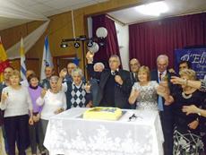 La directiva y socios alrededor de la tarta por el aniversario de la entidad.