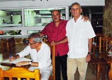 Víctor Gijón Peñas firma en el libro de honor acompañado por los directivos de la Casa de Cantabria Reinaldo Rojas y Andrés Liaño.