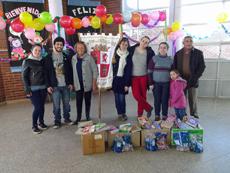 Los jóvenes con los regalos que llevaron al centro educativo.