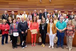 Silvia Clemente, en el centro de rojo, con el grupo de emigrantes que visitaron las Cortes de Castilla y León.