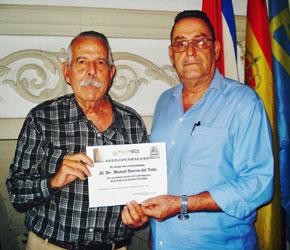 Manuel Barros (izquierda) recibió el Diploma de Reconocimiento de manos del presidente de la entidad, Armando L. Estévez.