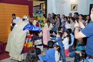 Los Reyes Magos entregando los juguetes a los niños.