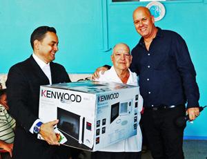 Sergio Toledo, derecha, en el momento de entregar el gran premio de la rifa, el horno microondas.