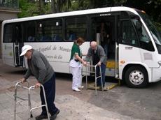 Un grupo de emigrantes bajan del autobús que los lleva al Centro de Día del Hogar Español.