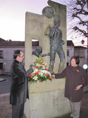 El alcalde Jorge Tuñas y una emigrante retornada en la ofrenda floral ante el Monumento al Emigrante.