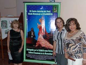Dirigentes de la comunidad andaluza en Perú junto al cartel de la exposicón de flamenco.