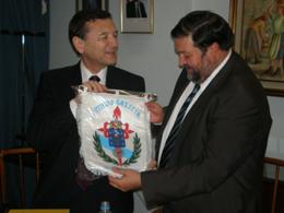 El presidente del Centro Galicia, José María Vila Alén, le entrega a Caamaño el banderín de la institución.