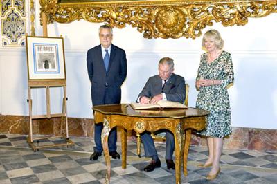 El Príncipe de Gales y la Duquesa de Cornualles firman en el Libro de Honor de la Junta en presencia de Griñán.