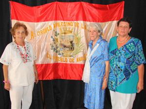 Mª A. Marcos Alonso, Ángeles Mª Vega Fernández y Mª Asunción Álvarez Fernández, principales directivas de la entidad con la mítica bandera detrás.