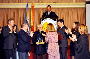 El artista, de origen gallego, Pepe Montoya recibe el Premio Colón de manos de la embajadora.