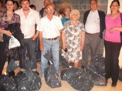 Los beneficiarios de las ayudas junto a las bolsas con alimentos.