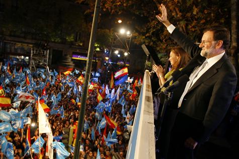 Mariano Rajoy saluda a los simpatizantes del PP desde el balcón de la sede del partido acompañado de su mujer.