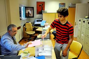 Un joven español deposita su voto en la urna en el Consulado en Montevideo.