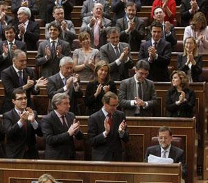 Mariano Rajoy, tras desgranar los planes de su Gobierno en el debate de investidura, recibe sentado el aplauso de los diputados 'populares', entre los que se encuentra (tercero por la izquierda en la fila superior) el director del PP en el Exterior, Alfredo Prada.