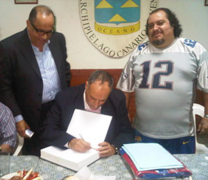 Firma el libro de visitantes. A la izquierda, Jacinto Pérez, delegado del gobierno de Canarias en Venezuela; y a la derecha Carmelo Hernández, presidente del Club Archipiélago Canario.