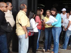 La precandidata María Corina Machado a las puertas     de la Fiscalía General de Venezuela rodeada por periodistas y afectados, revisa los expedientes ante de su denuncia.
