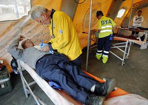 Un médico español atiende a una persona en el hospital de campaña instalado en la localidad chilena de Penco. (Foto: EFE)