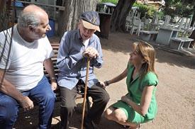 María Dolores de Cospedal dialoga en el Hogar Español con un anciano que cumplirá cien años.