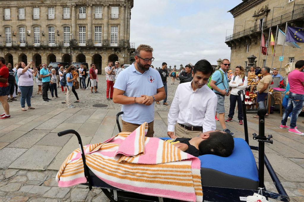 El conselleiro de Política Social, José Manuel Rey Varela, dio la bienvenida en la Praza do Obradoiro a las entidades de discapacidad Anpehi y Asprodeme tras finalizar el Camino de Santiago. Uno de los participantes, con una discapacidad del 99%, es la primera persona que realiza el Camino en una cama adaptada.